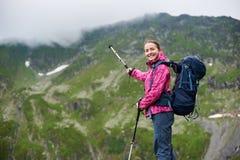 Hiker указывая с trekking ручкой на горе стоковое фото