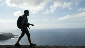 Hiker человека с рюкзаком идет на краю дороги в Канарских островах над океаном Тенерифе сток-видео