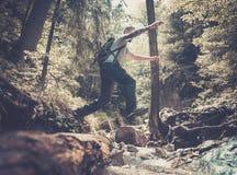 Hiker человека скача через поток стоковое изображение rf
