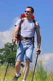 Hiker. Going on grassy meadow with unfocused tree and blue sky with clouds Stock Photos