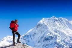 Hiker вверху утес с рюкзаком наслаждается солнечным днем Стоковое фото RF