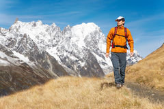 Hiker. Male trekker walks along a mountain path, in background the Grand Jourasses peaks, fall season; Val Veny, Mont Blanc massif, Courmayeur, Italy Stock Photo