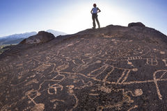Hiker admires native american rock art. Royalty Free Stock Images