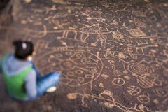 Hiker admires native american rock art. Stock Images