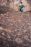 Hiker admires native american rock art. Stock Image