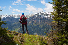 Hiker admires a panorama of mountains Royalty Free Stock Image