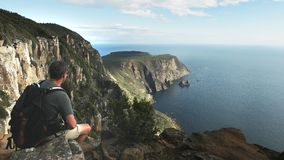 A hiker admires the view of cape raoul in tasmania. A hiker admires the view of the cliffs at cape raoul, part of the three capes experience, in tasmania stock footage