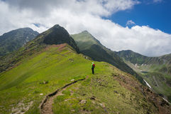 Hiker admiring the view on a path in the mountains Stock Images
