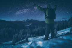 Hiker against starry night sky. Instagram stylisation. Hiker standing with raised hands against starry night sky with milky way above the winter mountain valley Stock Images