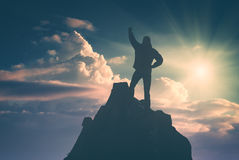 Hiker against the sun. Instagram stylisation. Hiker with raised hand standing on a cliffs edge against the sun. The top of the mountain. Colorful clouds in a stock images