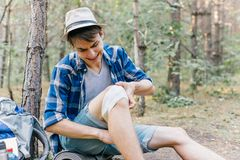 Hiker applying a bandage in a forest during the hike stock photos