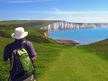 Hiker approaches white cliffs of Seven Sisters, East Sussex, England. A hiker approaches the Seven Sisters white chalk cliffs near Eastbourne in East Sussex royalty free stock image