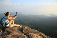 Hiker asian woman using digital tablet taking photo at mountain peak cliff Royalty Free Stock Photography
