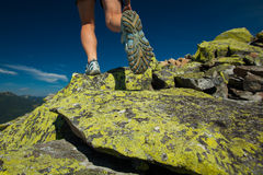 Hiker athlete is jumping over stones Stock Photos