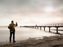 Hiker with backpack alone on sandy beach, sunrise above sea bridge. Royalty Free Stock Photos