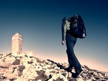 Hiker with backpack climbing on mountain peak. Summit stone in Alps Royalty Free Stock Photography