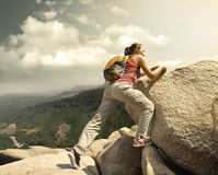Hiker with backpack crossing rocky terrain Stock Photo