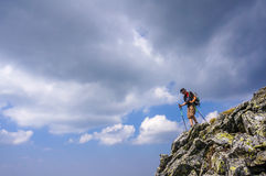 Hiker with backpack descending from the top of the mountain. Dramatic clouds Stock Image