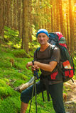 Hiker with backpack enjoying his travel, standing on the backgro Stock Photos