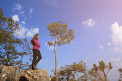 Hiker with backpack enjoying valley view from top of mountain. Royalty Free Stock Photos