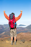 Hiker with backpack enjoying view from top of a mountain. Celebrating victory making it to the summit. Success and achievement concept Royalty Free Stock Photo