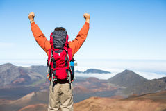 Hiker with backpack enjoying view from top of a mountain. Celebrating victory making it to the summit. Success and achievement concept Royalty Free Stock Image