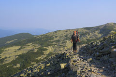 Hiker with backpack goes on rocky path in the mountains. Stock Photos
