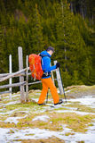 Hiker with backpack goes on the track. Royalty Free Stock Photo
