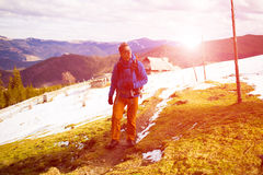 Hiker with backpack goes on the track. Royalty Free Stock Photography