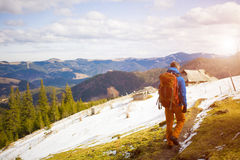 Hiker with backpack goes on the track. Stock Photos
