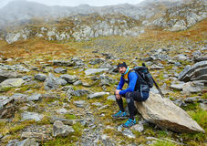 Hiker with backpack having a break Royalty Free Stock Image