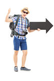 Hiker with backpack holding a big arrow and giving thumb up Stock Images