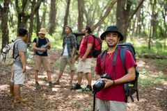 Hiker with backpack holding camera. Portrait of hiker with backpack holding camera and smiling Royalty Free Stock Photography