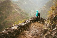 Hiker with backpack on the mountain edge cobbled path looking down the valley. Rocky terrain of high mountain ranges and. Deep ravines around him. Santo Antao Royalty Free Stock Images