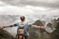 Hiker with backpack in mountains enjoying on view of foggy mount Royalty Free Stock Photo