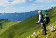 Hiker with backpack in a mountains Royalty Free Stock Photos