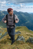 Hiker with backpack on mountains. Man hiking with backpack into the mountains Royalty Free Stock Photo