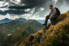 Hiker with backpack on mountains. Man hiking with backpack into the mountains Stock Image