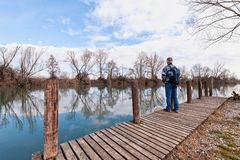 Hiker with backpack over wood pier on shore of river. Nature landscape. Senior hiker with backpack over the wood pier on shore of river Stock Photos
