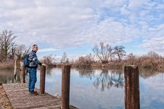 Hiker with backpack over wood pier on shore of river. Nature landscape. Senior hiker with backpack over the wood pier on shore of river Royalty Free Stock Photography