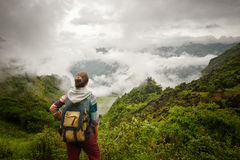 Hiker with backpack relaxing and enjoying on view of foggy mount Stock Image