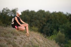Hiker with backpack relaxing on the grass. Eco tourism concept i. The Hiker with backpack relaxing on the grass. Eco tourism concept image with happy female royalty free stock photo