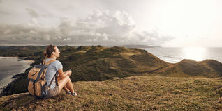 Hiker with backpack relaxing on top of mountain and enjoying pan Royalty Free Stock Image