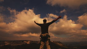 Hiker with backpack relaxing on top of a mountain and enjoying sunrise stock video footage