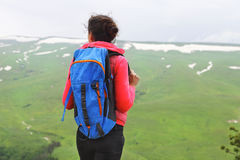 Hiker with backpack relaxing on top of a mountain and enjoying v Royalty Free Stock Photography