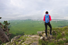 Hiker with backpack relaxing on top of a mountain and enjoying v Stock Photography
