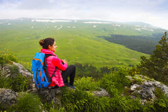 Hiker with backpack relaxing on top of a mountain and enjoying v Stock Photo