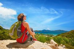 Hiker with backpack relaxing on top of the mountain and enjoying Stock Image
