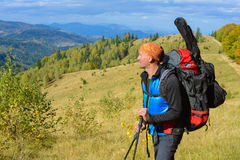 Hiker with backpack is resting , enjoying landscape in the autum Stock Image