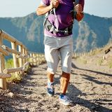 Hiker with backpack running on a path of mountain Royalty Free Stock Image